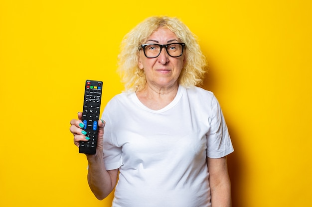 Smiling blonde old woman in eyeglasses holding remote control