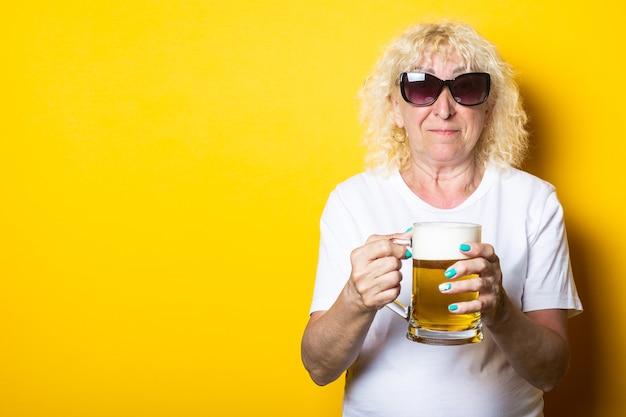 맥주 한 잔을 들고 선글라스에 흰색 티셔츠에 금발 늙은 여자를 웃고