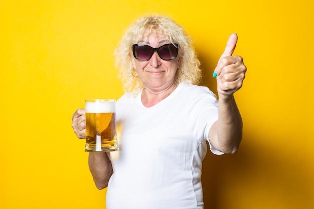 선글라스에 웃는 금발의 늙은 여자는 맥주 한 잔을 보유하고 제스처 클래스를 보여줍니다