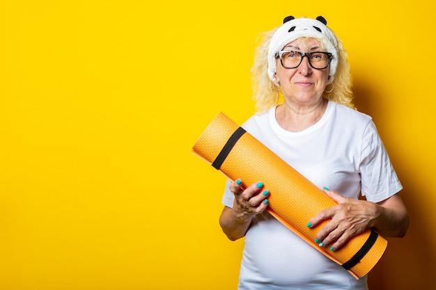 白いtシャツとメガネで笑顔の金髪の老婆はヨガマットを保持します