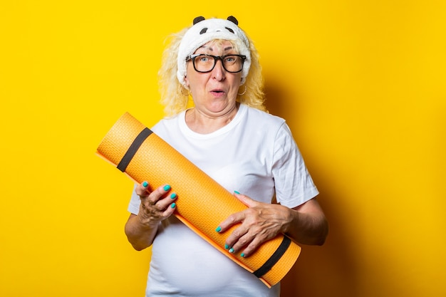 Smiling blonde old woman in white t-shirt and glasses holds yoga mat