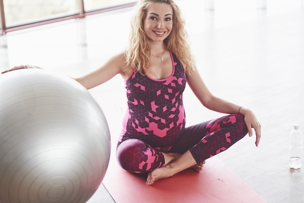 Smiling blonde pregnant woman in pink sitting on the fitness mat holding the stability ball by right hand.