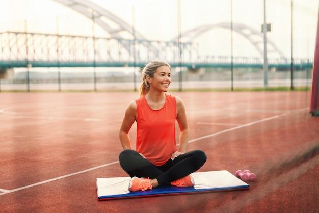 Улыбающаяся белокурая спортивная женщина, сидящая на циновке со скрещенными ногами