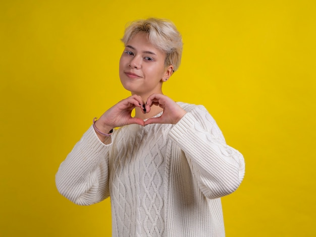 手でハートのジェスチャーを作る白いニットセーターで白い髪の金髪の十代の少女の笑顔