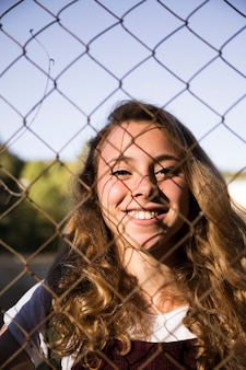 Smiling blonde through chain link