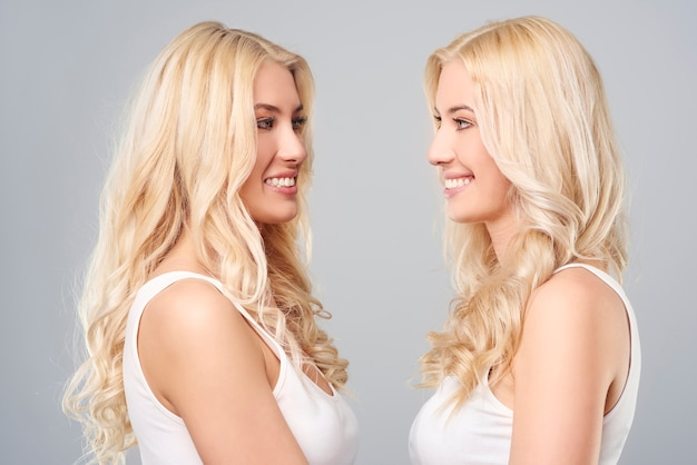 Smiling blonde twins standing face to face