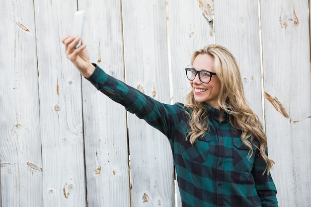 Smiling blonde with glasses taking a selfie