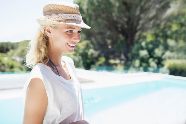 Smiling blonde with hat looking away