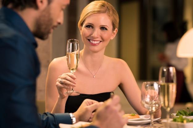 彼女のボーイフレンドと一緒に高級レストランで笑顔の金髪の女性は彼らの記念日を祝います。