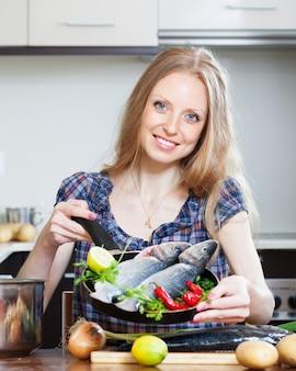 フライパンでlubinaを料理しているブロンドの女性を笑って