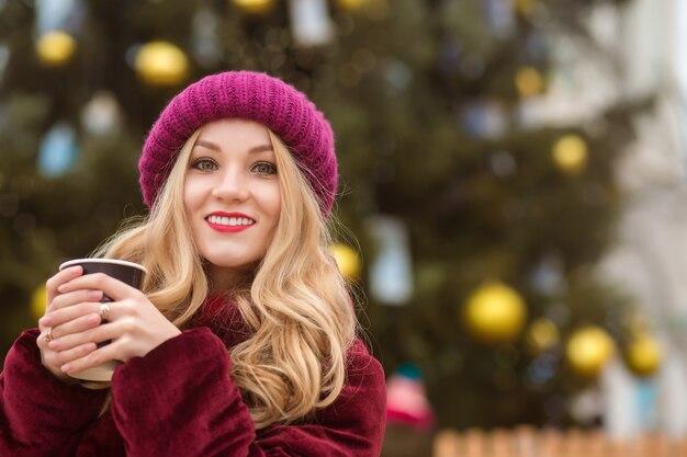冬の服を着て、クリスマスツリーでコーヒーを飲む金髪の女性の笑顔