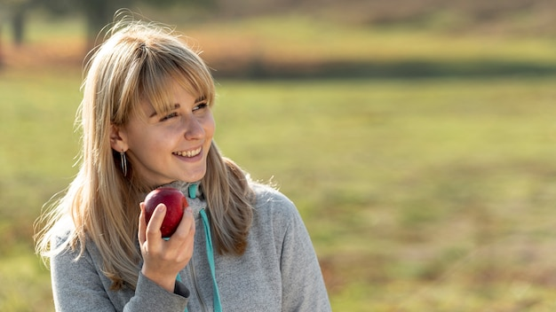Smiling blonde woman eating a delicious apple
