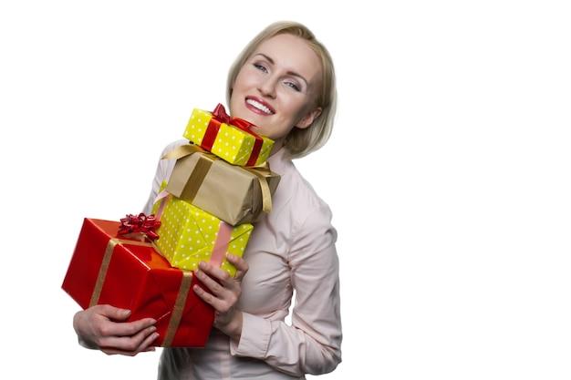 흰 벽에 선물 상자를 많이 들고 웃는 금발의 여자