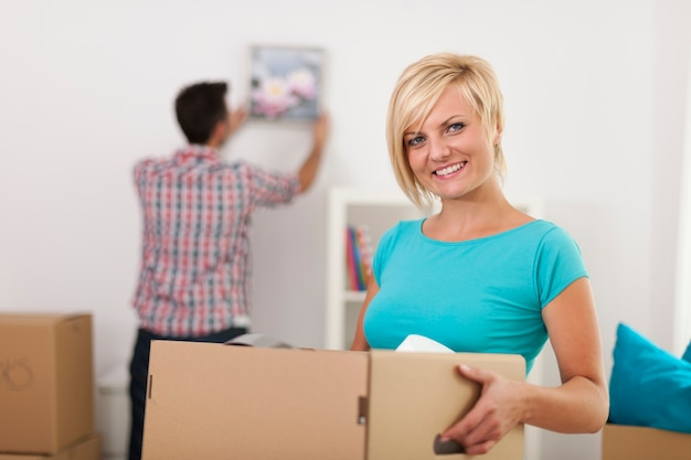 Улыбающаяся блондинка женщина, держащая картонную коробку во время переезда домой