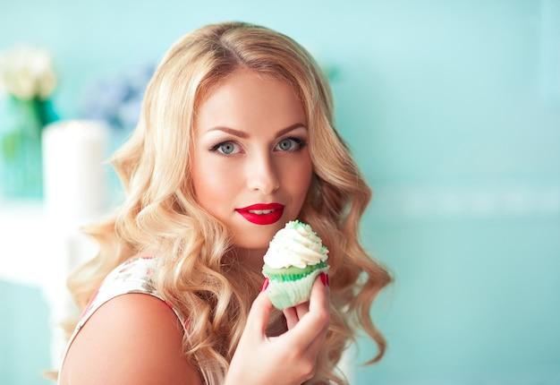 맛있는 컵케이크를 들고 웃는 금발의 여자