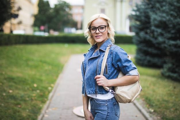 Улыбающаяся блондинка в портрете в очках в городе, одетом в джинсовый люкс утром