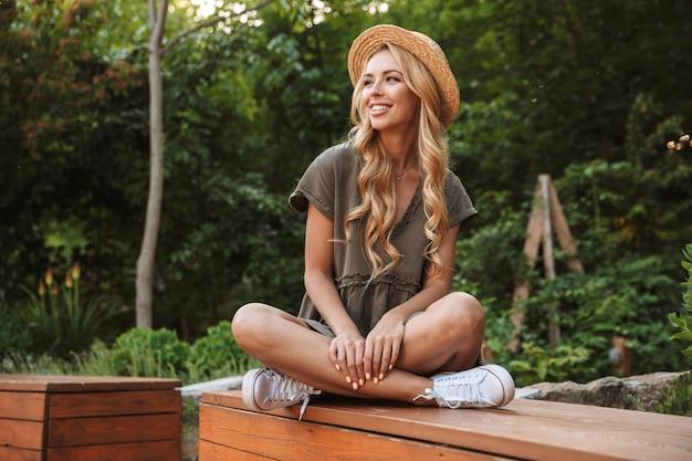 야외 벤치에 앉아있는 동안 멀리 찾고 밀짚 모자에 금발 여자를 웃고