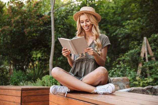 야외 벤치에 앉아있는 동안 책을 읽고 밀짚 모자에 웃는 금발의 여자