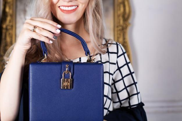 青い革の財布を保持しているサングラスで笑顔の金髪の女性。テキスト用のスペース