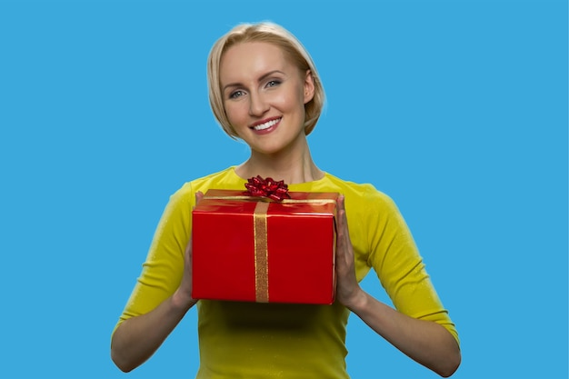 Smiling blonde woman is holding a red gift box