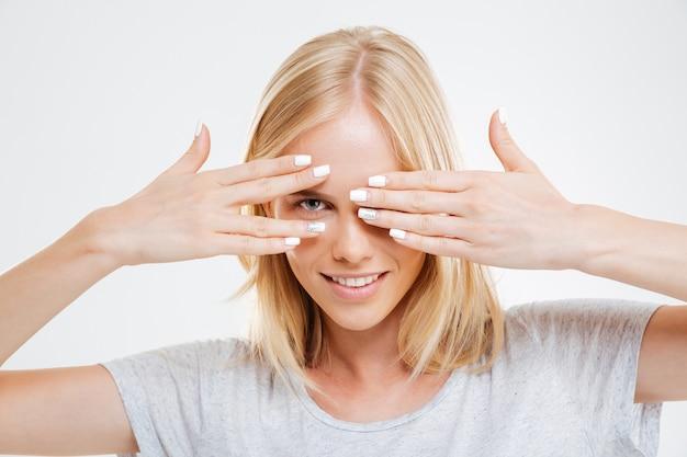 Улыбающаяся блондинка смотрит вперед сквозь пальцы, изолированные на белой стене