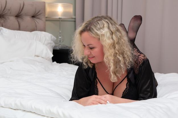 침대에 누워 웃는 금발 여자