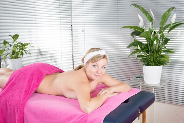 Smiling blonde woman in massage salon