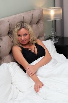 침대에 웃는 금발 여자