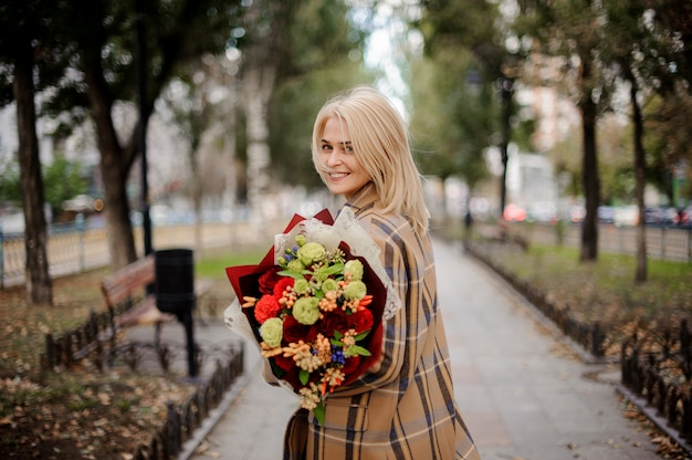 Smiling blonde woman in plaid coat holding a bright bouquet of flowers walking on alley