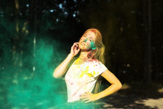公園で緑の乾いたペンキホーリーで遊んでいる金髪の女性の笑顔
