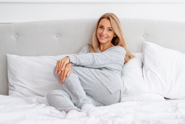Smiling blonde woman relaxing in bed