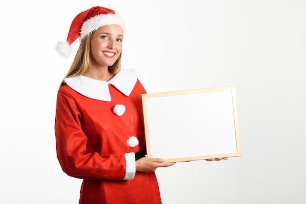 La donna bionda sorridente in vestiti di santa claus con la scheda bianca