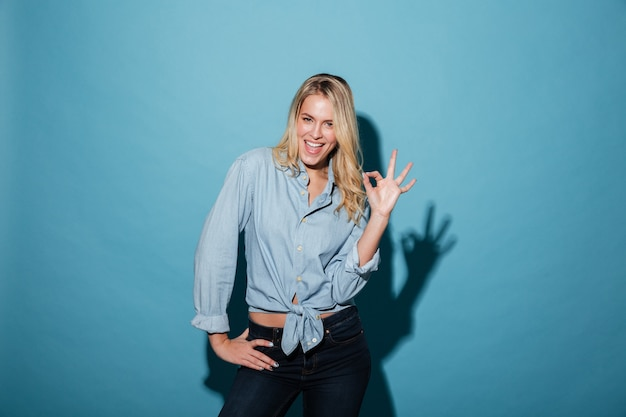 Smiling blonde woman in shirt holding arm on hip