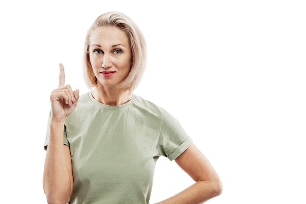 Smiling blonde woman showing index finger up.. space for text.