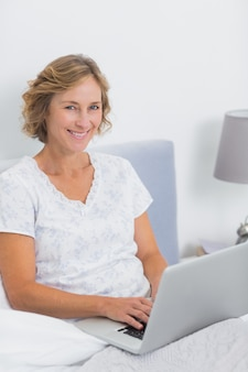 Smiling blonde woman sitting in bed using laptop