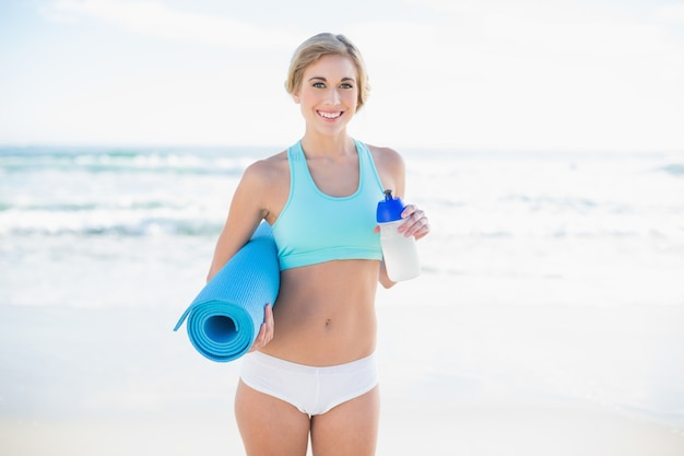Smiling blonde woman in sportswear holding a bottle and an exercise mat
