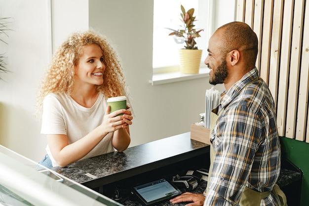 Улыбающаяся блондинка разговаривает с официантом кафе за столиком
