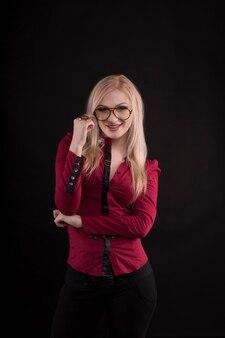 眼鏡をかけ、赤いブラウスに身を包んだ金髪の女性の笑顔