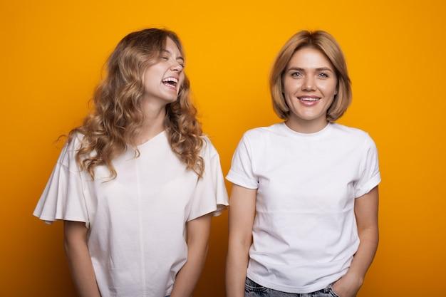 Улыбающаяся блондинка с вьющимися волосами позирует возле своей сестры на желтой стене в белой футболке