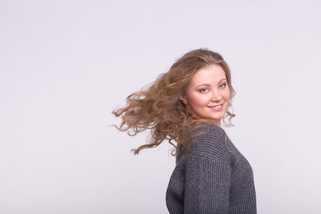 コピースペースと白い壁に飛んでいる髪と笑顔のブロンドの女性