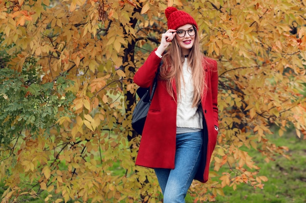 Smiling blonde woman with long hairs walking in sunny autumn park in trendy casual outfit.