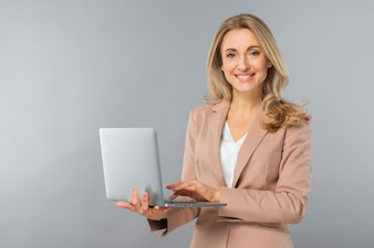 Smiling blonde young businesswoman using laptop in hand against gray backdrop