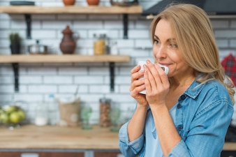 Smiling blonde young woman drinking coffee from white cup in the kitchen