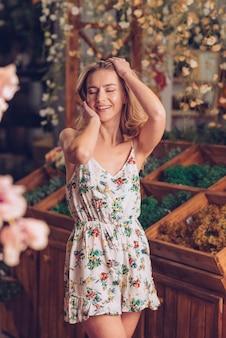 Giovane donna bionda sorridente in vestito floreale che posa al negozio di fiorista
