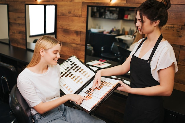 Smiling blonde young woman and hairdresser choosing hair color from palette