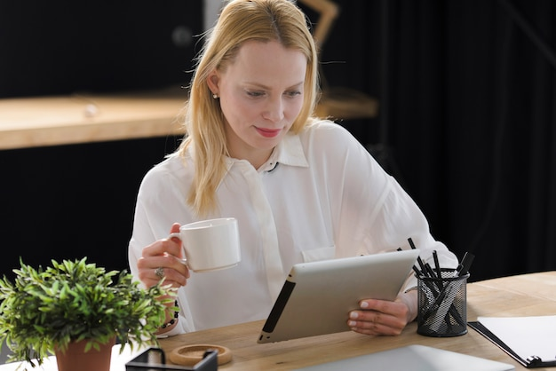 Smiling blonde young woman holding cup of coffee looking at digital tablet