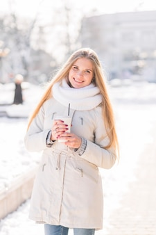 Smiling blonde young woman holding disposable coffee cup in winter
