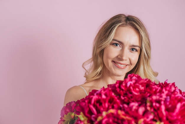 Smiling blonde young woman holding flower bouquet