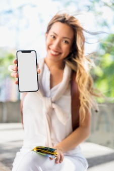 Smiling blonde young woman holding map in hand showing mobile blank white screen