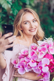Smiling blonde young woman holding orchid in hand taking self portrait from mobile phone